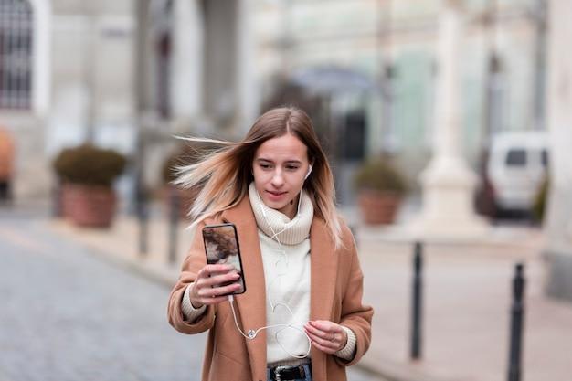 Moderne jonge vrouw die aan muziek op oortelefoons buiten luistert