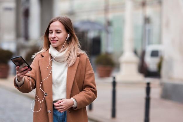 Moderne jonge vrouw die aan muziek op oortelefoons luistert met exemplaarruimte