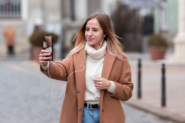 Moderne jonge vrouw die aan muziek op oortelefoons luistert terwijl het nemen van een selfie