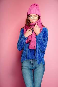 Moderne jonge vrouw die blauwe sweater en roze hoed draagt, en sjaal stelt, die grappige gelaatsuitdrukking maakt.