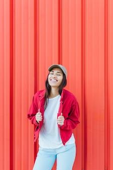 Moderne jonge vrouw die zich voor rode golfachtergrond bevindt