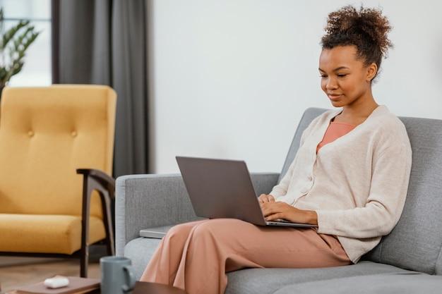Moderne jonge vrouw die zittend op de bank werkt