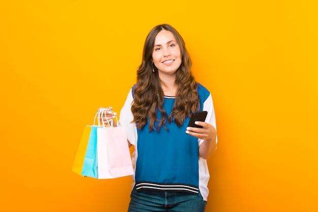 Moderne jonge vrouw gebruikt haar telefoon om te winkelen.