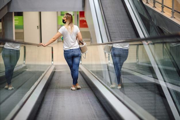 Moderne jonge vrouw in wit t-shirt en jeans op roltrap in winkelcentrum kijkt rond. winkelen en plezier. levensstijl. het dagelijkse leven in de stad. goederen en consumptie.