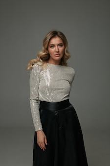 Moderne jonge vrouw in zwarte maxirok en zijden witte blouse