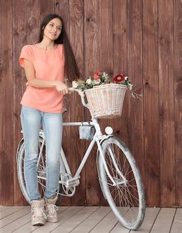 Moderne jonge vrouw met fiets en lentebloemen in mand