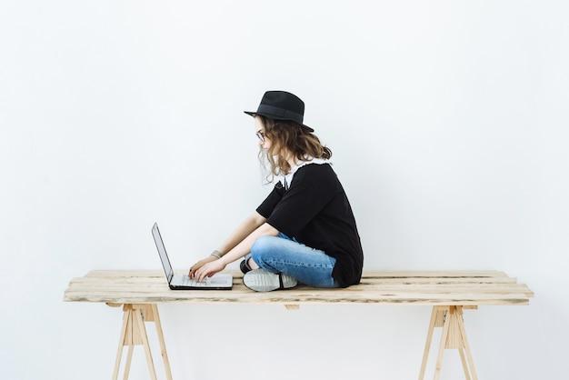 Moderne jonge vrouw met hoed en bril werkt op een laptop terwijl ze op een tafel in een witte kamer zit