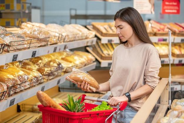 Moderne jonge vrouw met lang haar die 's ochtends brood in de supermarkt kiest