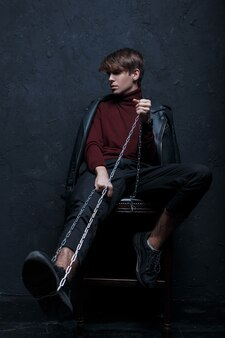 Moderne jongeman in een modieus jasje in vintage bordeauxrode golf in trendy jeans en zwarte sneakers met een metalen ketting zit op een houten stoel in een kamer in de buurt van een zwarte muur. knappe stijlvolle kerel