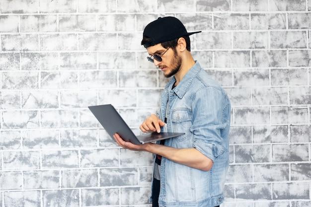 Moderne jongeman met laptop in handen op muur van bakstenen muur.