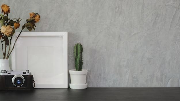 Moderne kantoorruimte met mock up frame, camera en kantoorbenodigdheden op zwarte tafel en grijze muur