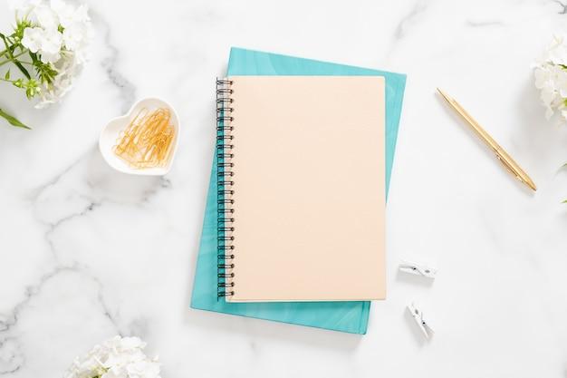 Moderne kantoorwerkplek aan huis met blanco papieren notitieblok, witte bloemen en vrouwelijke accessoires