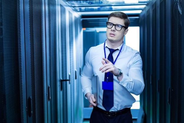 Moderne kasten. vastberaden professionele operator die een laptop vasthoudt en op zoek is naar de juiste serverkast