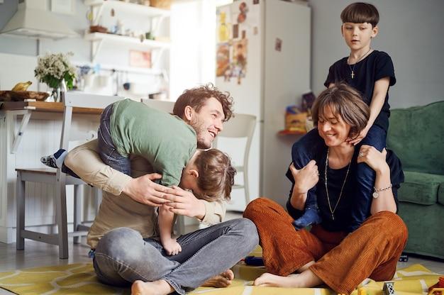 Moderne kaukasische en gelukkige familie hebben plezier en tijd met zonen thuis ouders spelen met kinderen