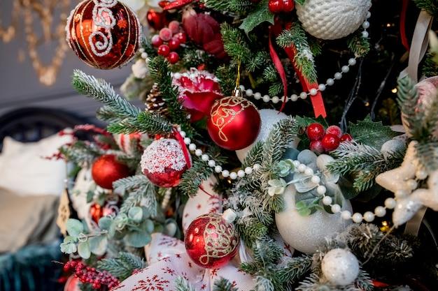 Moderne kerstboom, versierd met vintage ornamenten, ratan ballen, jute en tartan linten, houten sneeuwvlokken, rode bessen en ballen, rode witte ballen. kerstballen.