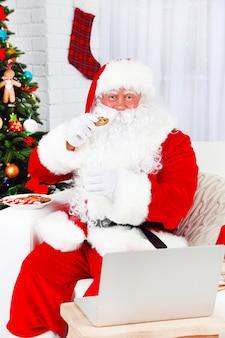 Moderne kerstman zittend op de bank en met behulp van computer