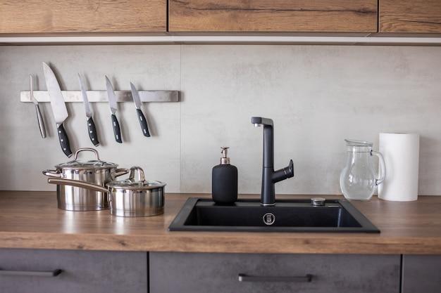 Moderne keuken in grijze kleuren en houten kasten thuis met keukengerei