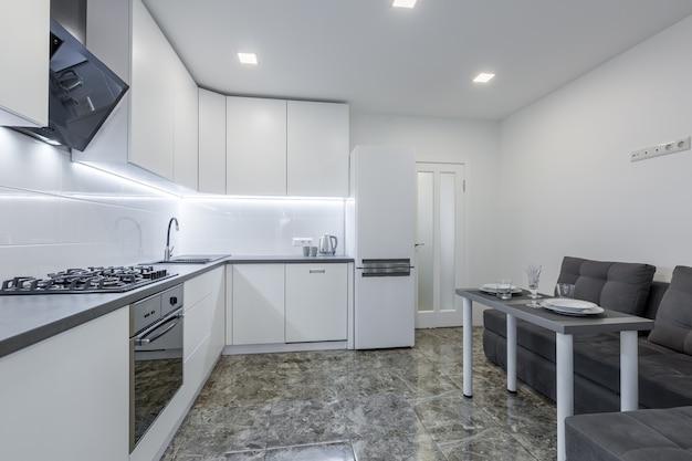 Moderne keuken in lichte witte tinten met zwarte marmeren tegels op de vloer geplaatst in een klein appartement