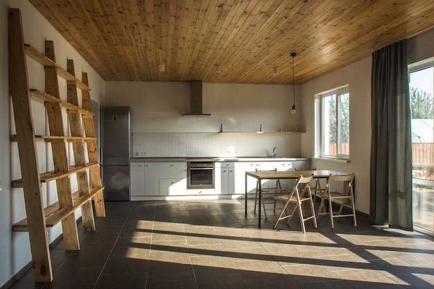 Moderne keuken met meubilair in grijze kleur en houten tafelblad, stijlvol keukeninterieur in scandinavische stijl