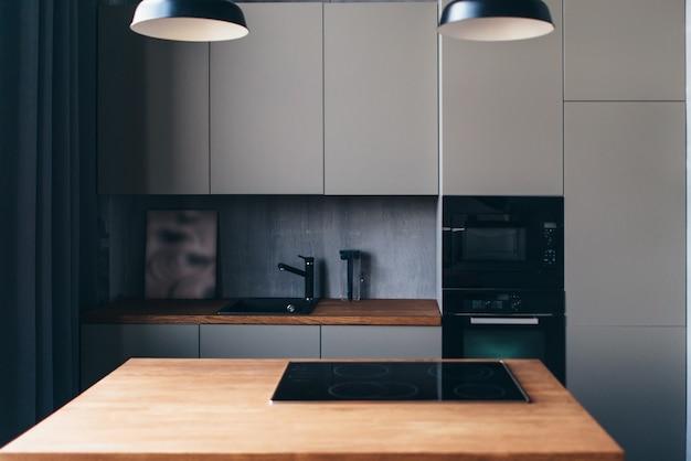 Moderne keuken met tafel en ingebouwde kookplaat. interieur ontwerp.