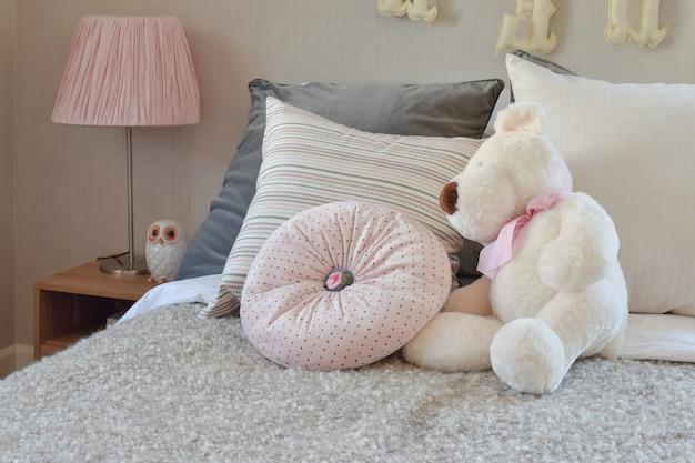 Moderne kinderkamer met pop en kussens op bed