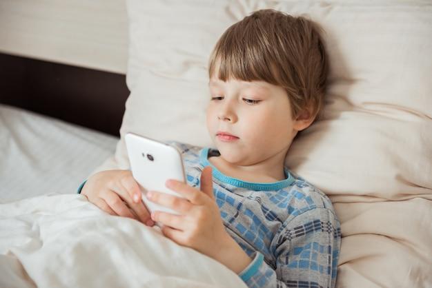 Moderne klein kind ligt op bed met smartphone in zijn handen