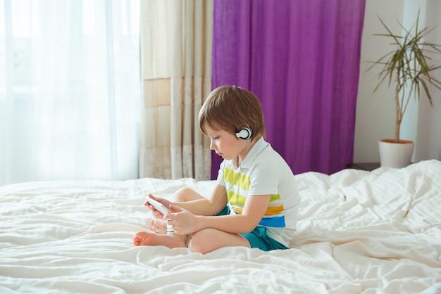 Moderne klein kind zittend op bed met smartphone in zijn handen