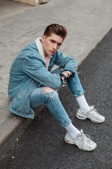 Moderne knappe jongeman in mode witte sneakers in gescheurde vintage jeans in modieuze spijkerjasje zit op tegel in de buurt van weg op straat in de stad. cool stedelijke man in stijlvolle kleding rust buiten.
