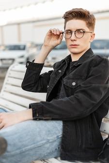 Moderne knappe jongeman in stijlvolle jeans kleding rechtzetten trendy bril. stedelijke stijlvolle man in casual denimkleding met trendy kapsel zit op houten bankje op straat. jeugd mode herenkleding.