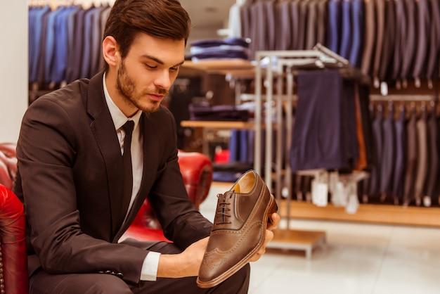 Moderne knappe zakenman die klassieke schoenen houdt.