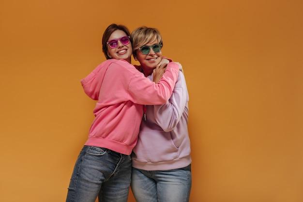 Moderne kortharige dames met geknipte glimlach en roze en groene bril in brede stijlvolle hoodies op oranje geïsoleerde achtergrond.