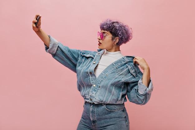 Moderne kortharige vrouw met een helder kapsel in roze bril maakt selfie. mooie krullende vrouw in denim jasje poseren.