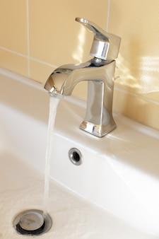 Moderne kraan in gele badkamer met stromend water