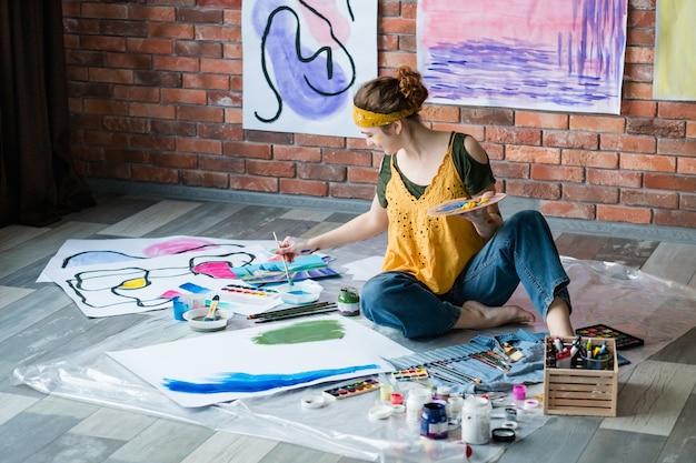 Moderne kunstacademie. vrouwelijke artiest zittend op de vloer, schilderij abstracte kunstwerken