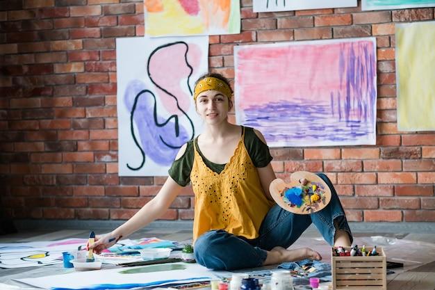 Moderne kunsttentoonstelling. vrouwelijke kunstenaar schilderen, zittend op de vloer over haar abstracte kunstwerken die op bakstenen muur hangen.