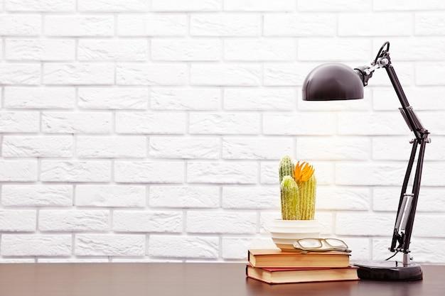 Moderne lamp en boeken op het bureau op witte muurachtergrond