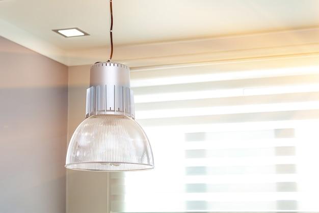 Moderne lamp met een grote glazen plafondkap onder het plafond van het universele kantoor.
