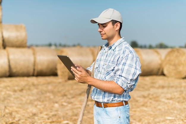 Moderne landbouwer die zijn tablet gebruikt