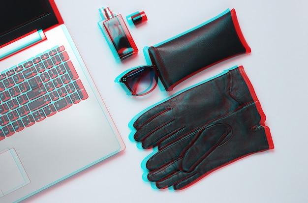 Moderne laptop, damesaccessoires op grijze achtergrond. glitch-effect. bovenaanzicht