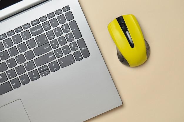 Moderne laptop, draadloze muis op een gele pastel achtergrond, minimalisme, bovenaanzicht, plat lag