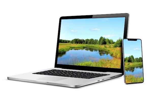Moderne laptop en smartphone met landschapsbehang op scherm