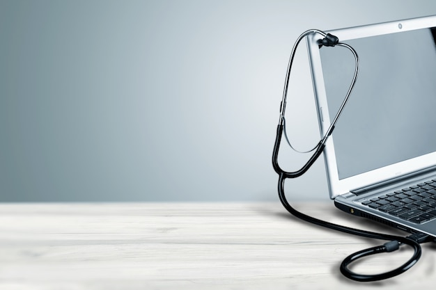 Moderne laptop en stethoscoop op de achtergrond, vergrote weergave