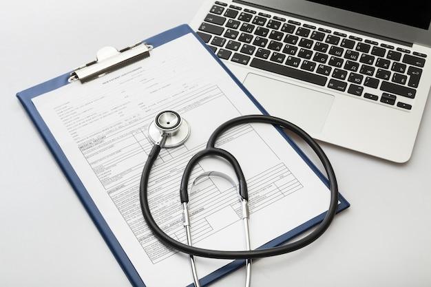 Moderne laptop en stethoscoop op houten achtergrond