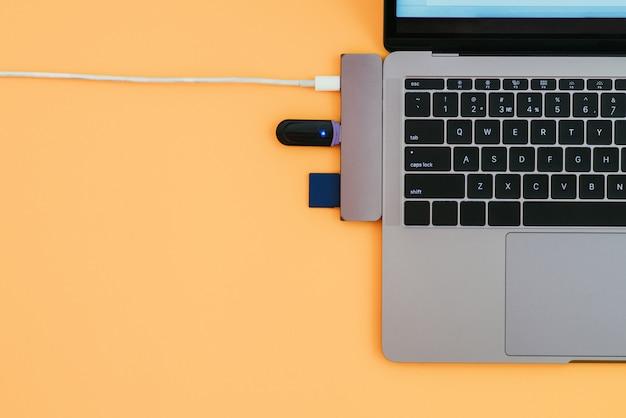 Moderne laptop, usb type-c-adapter met flitser en opladen op oranje oppervlak
