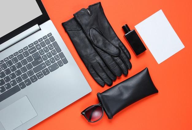 Moderne laptop, vrouwen accessoires en vel wit papier voor kopie ruimte op oranje tafel. bovenaanzicht
