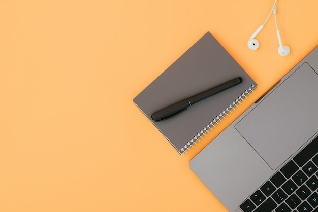 Moderne laptop, witte koptelefoon en een grijze notebook met een pen op het oranje oppervlak