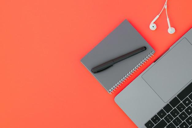 Moderne laptop, witte koptelefoon en een grijze notebook met een pen op het rode oppervlak
