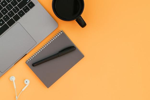 Moderne laptop, witte koptelefoon, grijze notebook met een pen en een kopje koffie op het oranje oppervlak