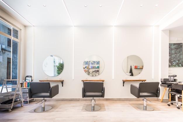 Moderne lichte schoonheidssalon. kapsalon interieur bedrijf met zwarte stoelen, ronde spiegels en neonlichten.