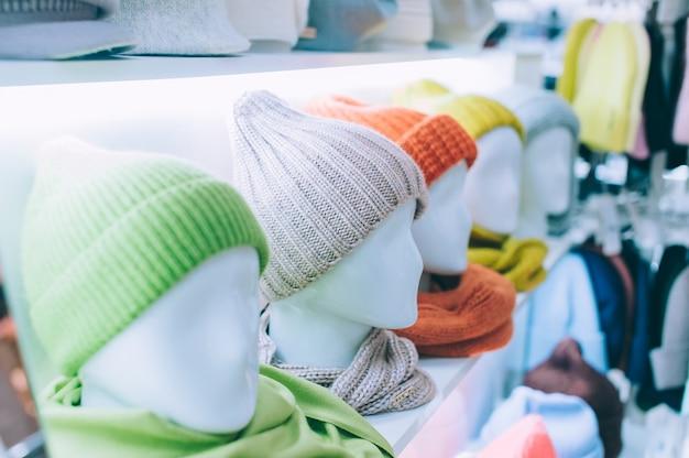 Moderne lichte wintermutsen, met sjaals op de hoofden van mannequins in een supermarktvitrine.